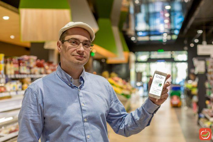 Ivo Dimitrov, holding CozZo app in a supermarket.